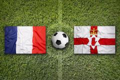 France vs. Northern Ireland flags on soccer field - stock photo