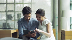 Couple reading news on digital tablet Stock Footage