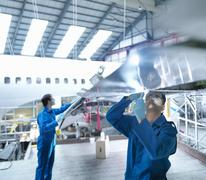 Engineers working on aircraft wing in aircraft maintenance factory - stock photo