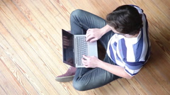 Man using laptop computer while sitting on hardwood floor Stock Footage
