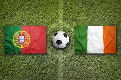 Portugal vs. Ireland flags on soccer field - stock photo