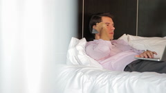 Man reclining on bed using laptop, chatting on cell phone Stock Footage