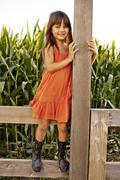 Portrait of girl standing and holding onto field fence Stock Photos