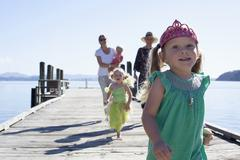 Two mid adult women and daughters strolling and running on pier, New Zealand - stock photo