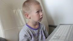 Child looks cartoons on the computer Stock Footage