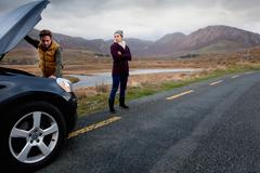 Couple by stalled vehicle at roadside, Connemara, Ireland Stock Photos