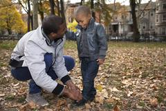 Young man tying toddler sons shoelace in park - stock photo