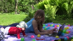 Baby kid interrupt loving mother work with computer on plaid in garden. 4K Stock Footage