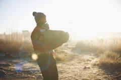 Man holding log in rural landscape - stock photo