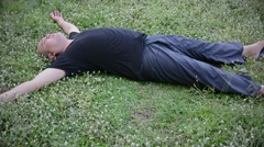 An unconscious fat bald head Thai man drop himself on the grass in HD quality Stock Footage