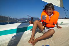 Portrait of young boy on boat wearing life jacket Stock Photos