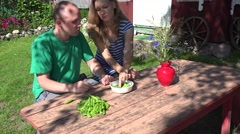 Young couple eat green hulled peas in country background. 4K Stock Footage