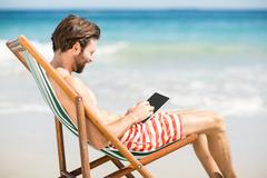 Man sitting on armchair at beach - stock photo