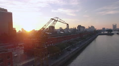 Construction crane on city riverbank backlit by setting sun - stock footage
