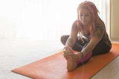 Young woman with pink dreadlocks practicing yoga on yoga mat Stock Photos