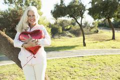 Senior woman hugging red heart-shaped balloon, Hahn Park, Los Angeles, - stock photo
