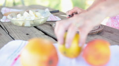 Cutting orange to add juice to apple and pear mixture Stock Footage