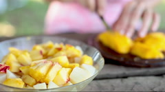 Cutting mango to add to fruit salad Stock Footage