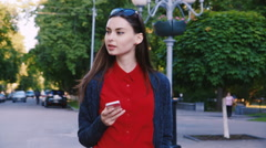 Attractive woman walking down the street, enjoying smartphone Stock Footage