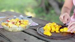 Adding chopped mango to fruit salad Stock Footage