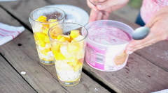 Topping fruit salad with ice cream and chocolate shavings Stock Footage