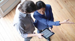 Couple looking at blueprint on digital tablet - stock footage