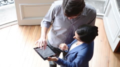 Man explaining floor plan on digital tablet to woman - stock footage