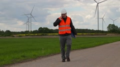 Electrician engineer walking and talking on smart phone near Windmills Stock Footage
