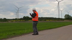 Electrician engineer walking and take pictures on smart phone near Windmills Stock Footage