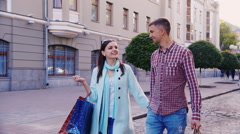 A man and a woman walking on a city with shopping bags Stock Footage