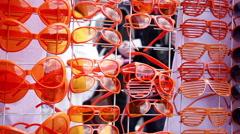 Souvenir shop selling orange sunglasses in Amsterdam, Netherlands Stock Footage