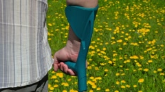 Disabled man with crutches on the dandelion field Stock Footage