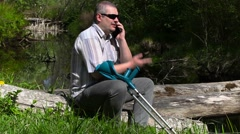 Disabled man with crutches talking on smart phone near river Stock Footage