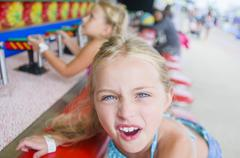 Portrait of girl pulling faces at fairground stall Stock Photos