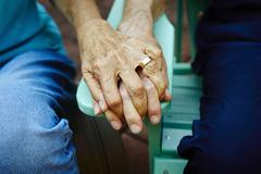 Cropped close up of senior couple hands holding on park bench Stock Photos