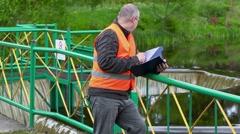 Engineer writing near floodgate - stock footage