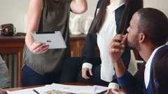 Colleagues looking at digital tablet during casual business meeting Stock Footage