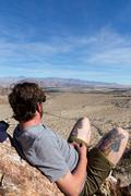 Young man on rocks looking out at landscape, Anza-Borrego Desert State Park, Stock Photos