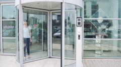Woman exiting building through revolving door Stock Footage