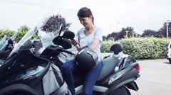 Woman sitting on motorcycle making phone call - stock footage
