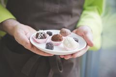 Waiter carrying plate of varying confectionery - stock photo