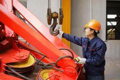 Worker using equipment in crane manufacturing facility, China Kuvituskuvat