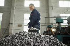 Worker shovelling metal components used in crane manufacturing facility, China Kuvituskuvat