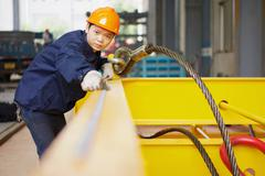 Worker using equipment in crane manufacturing facility, China - stock photo