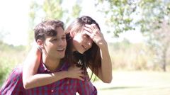 Young man giving his girlfriend a piggyback ride outdoors Stock Footage