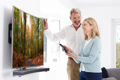 Mature Couple With New Curved Screen Television At Home - stock photo