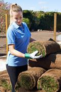 Female Landscape Gardener Laying Turf For New Lawn - stock photo