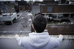 Depressed Young Man Contemplating Suicide On Top Of Tall Building - stock photo