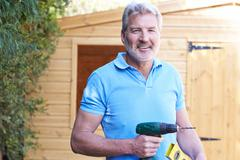 Handyman Standing Outside Garden Shed With Tools - stock photo