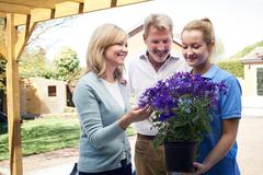 Landscape Gardener Advising Mature Couple On Garden Plants - stock photo